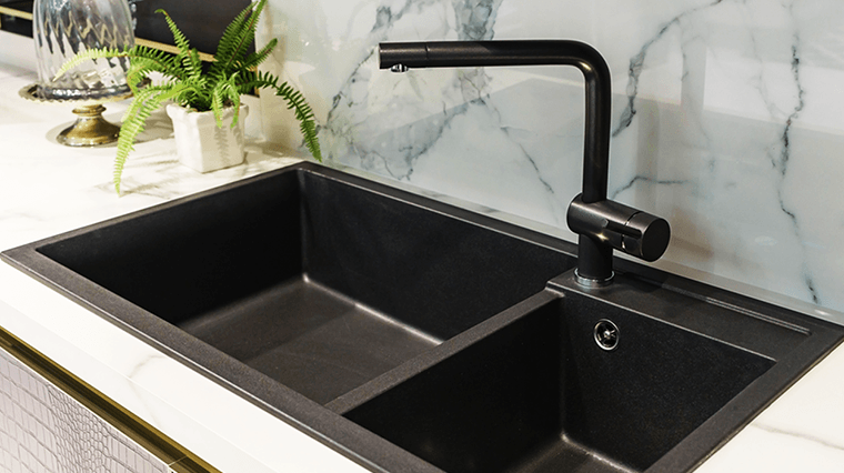 partitioned black kitchen sink and faucet