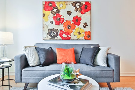 Having two subdued colors in your room and then having attention-drawing items be a much brighter color is a great and cozy way of decorating your living room
