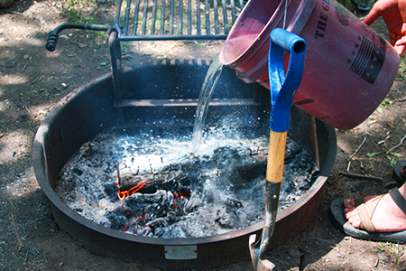 pouring water on campfire for fire saftey